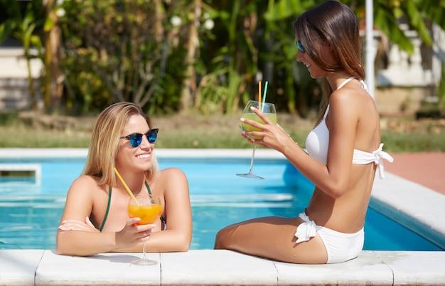 La donna che si rilassa e beve un cocktail alla piscina Foto Premium