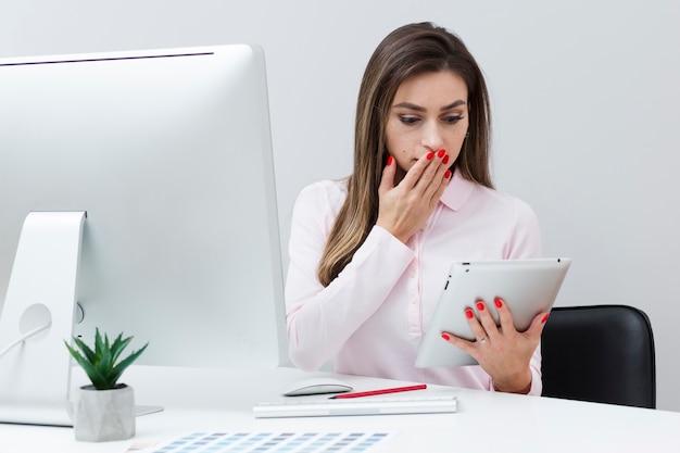 La donna colpita che esamina la sua compressa e copre la sua bocca Foto Gratuite