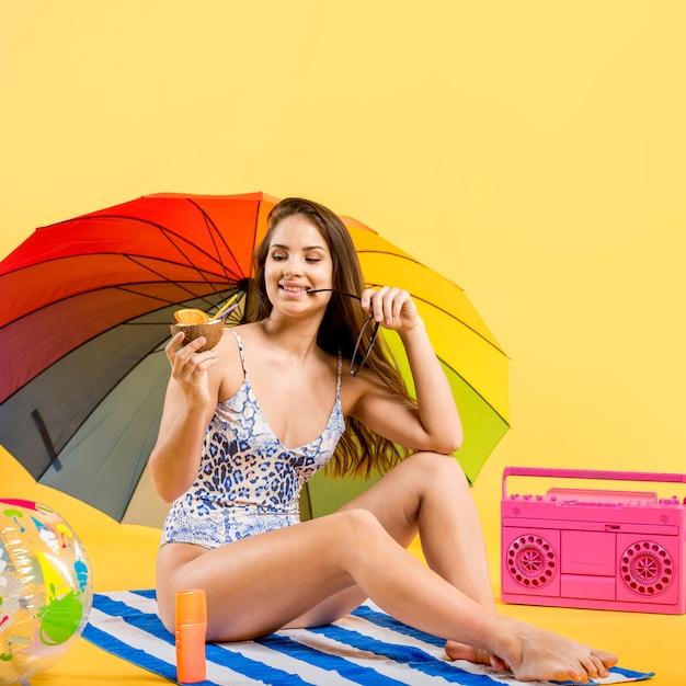 La donna con l'ombrello che si siede sulla stuoia della spiaggia e che gode della bevanda della noce di cocco Foto Gratuite