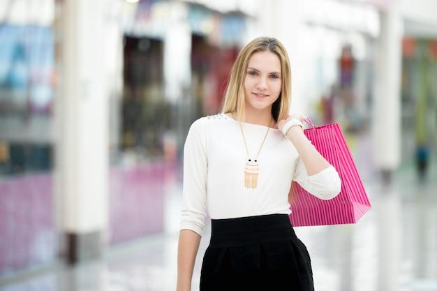 La donna con un sacchetto di acquisto di colore rosa Foto Gratuite
