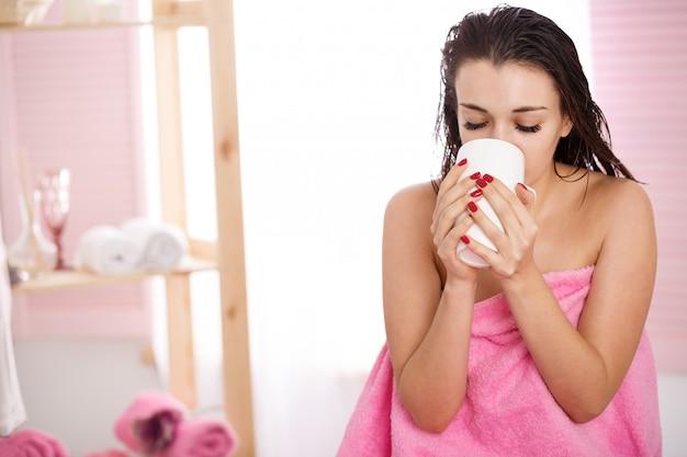 La donna coperta di asciugamano rosa beve il tè dopo il trattamento di bellezza Foto Gratuite