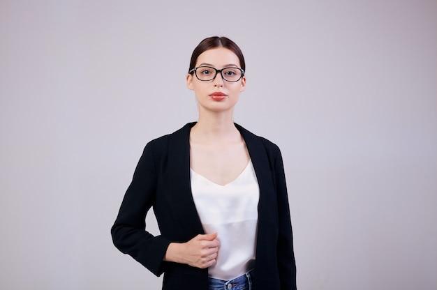 La donna d'affari dall'aspetto piacevole è in piedi sul grigio in una giacca nera, maglietta bianca e occhiali da computer. Foto Premium