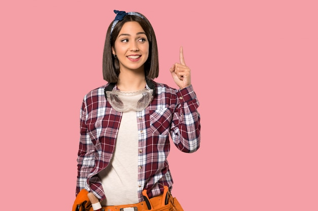 La donna del giovane operaio che intende realizzare la soluzione mentre solleva un dito sulla parete rosa isolata Foto Premium