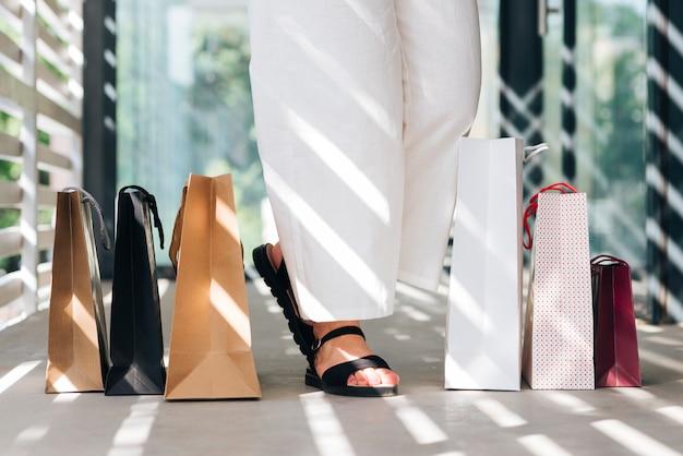 La donna del primo piano in sandali si avvicina ai sacchetti della spesa Foto Gratuite
