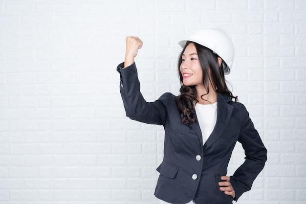 La donna dell'ingegneria che tiene un cappello, separa i gesti fatti del muro di mattoni bianco con la lingua dei segni. Foto Gratuite