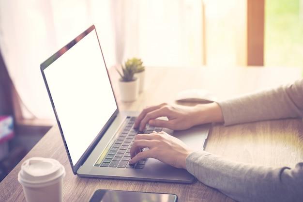 La donna di affari che per mezzo del computer portatile fa l'attività online sull'ufficio di legno della tavola a casa. Foto Premium