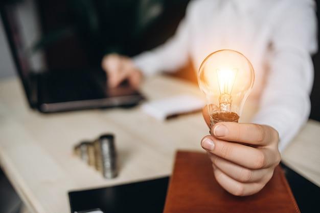 La donna di affari che tiene le lampadine sullo scrittorio in un ufficio e lavora per il computer. Foto Premium
