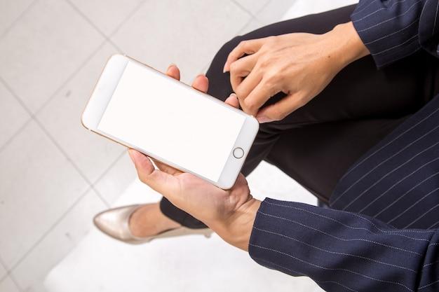 La donna di affari controlla le sue e-mail sul suo smartphone del dispositivo del telefono cellulare Foto Premium