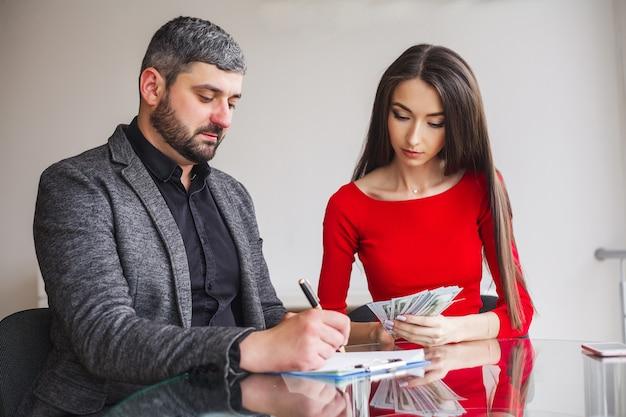 La donna di affari dà soldi agli uomini. Foto Premium