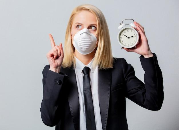 La donna di affari disperata in vestito nero e maschera facciale tiene la sveglia Foto Premium