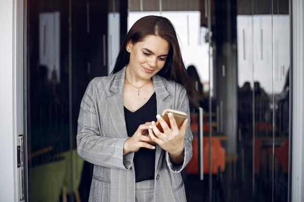 La donna di affari elegante che lavora in un ufficio e usa il telefono Foto Gratuite