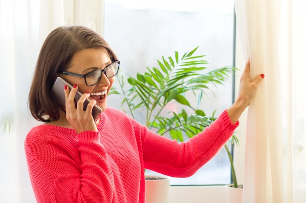La donna di mezza età sorridente sta parlando al telefono Foto Premium