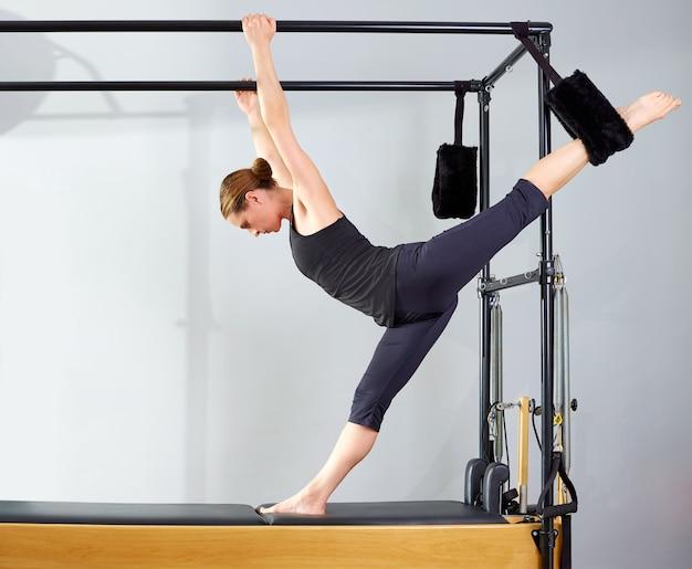 La donna di pilates in gambe divise cadillac allunga l'esercizio Foto Premium