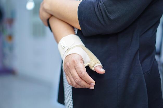 La donna di signora di mezza età asiatica usa la fasciatura elastica per trattare la sindrome di de quervain a portata di mano e il dito in ufficio. Foto Premium