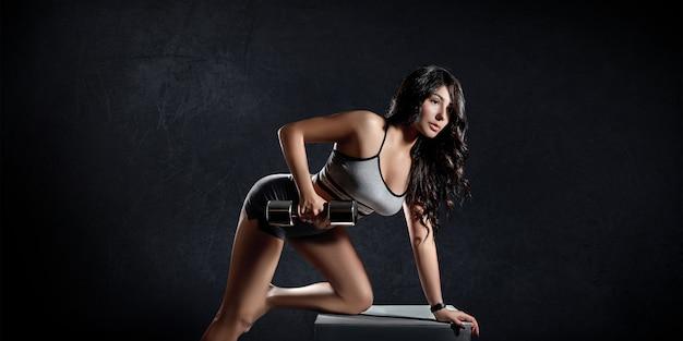 La donna di sport di forma fisica si prepara su un fondo scuro Foto Premium