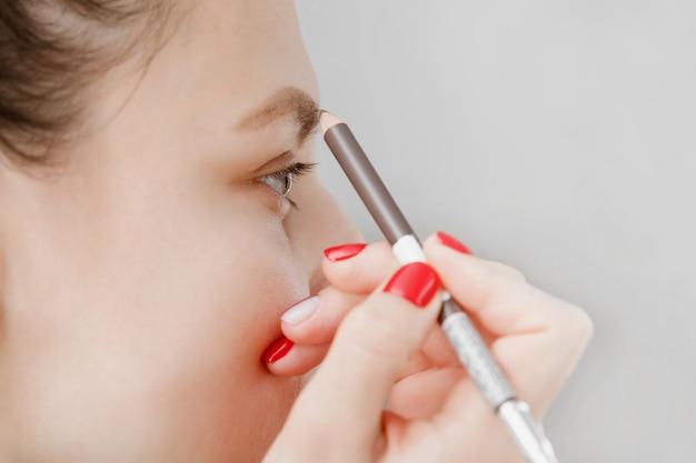 La donna dipinge le sopracciglia davanti allo specchio. bella ragazza vernice sopracciglia marrone. ragazza che fa trucco davanti ad uno specchio. la ragazza si stava prendendo cura del suo viso. Foto Premium
