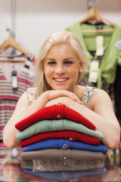 La donna è appoggiata sui vestiti e sorridente Foto Premium
