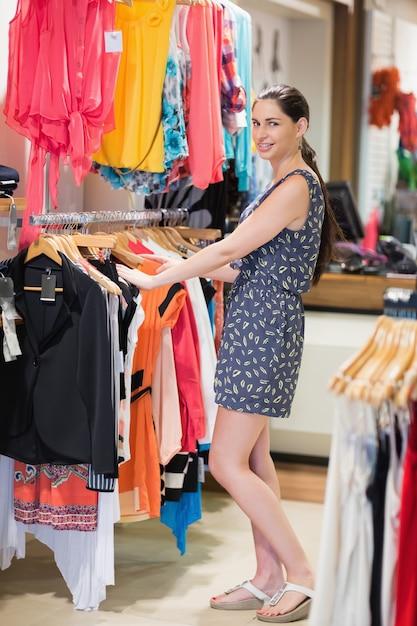 La donna è in piedi presso il rack di vestiti sorridendo Foto Premium