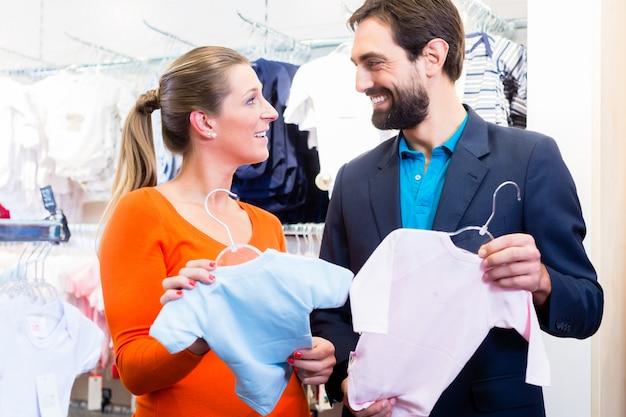 La donna e l'uomo si aspettano gemelli che comprano vestiti per bambini Foto Premium
