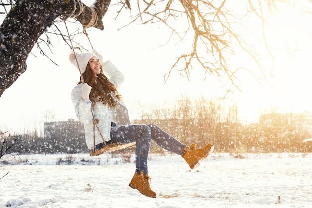 La donna e la corda felici oscillano nel paesaggio dell'inverno Foto Premium