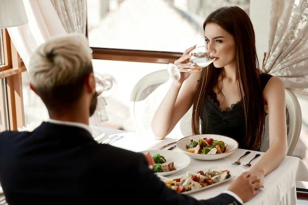 La donna e un uomo si tengono per mano per un appuntamento romantico al ristorante Foto Gratuite