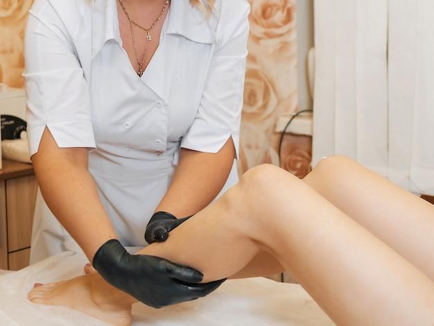 La donna estetista e massaggiatrice professionista si prende cura dei piedi del cliente ragazza Foto Premium