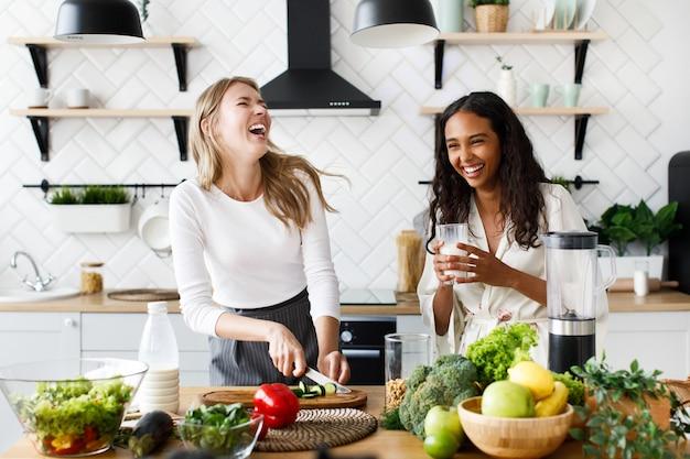La donna europea sta tagliando un cetriolo e la donna africana sta bevendo latte, ridono Foto Gratuite