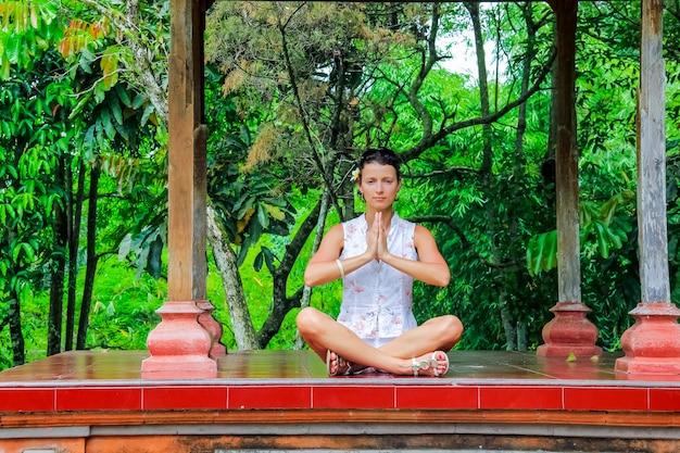 La donna felice che fa l'yoga si esercita all'aperto Foto Premium