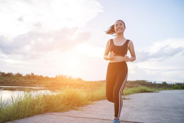 La donna felice del corridore funziona nell'esercizio pareggiante del parco. Foto Gratuite