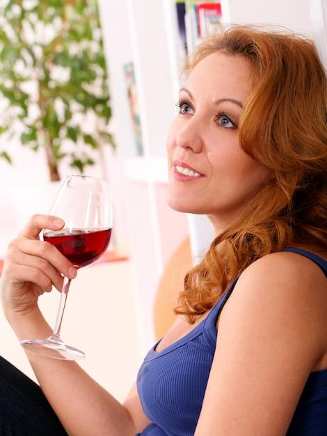 La donna felice di mezza età gode del bicchiere di vino Foto Gratuite