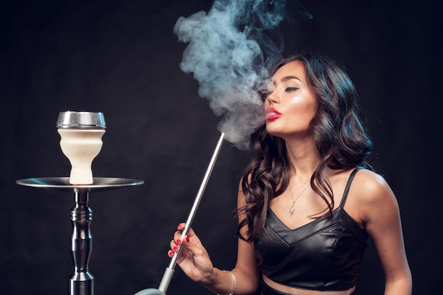 La donna fuma narghilè / bella donna affascinante in abito nero fuma un narghilè Foto Premium