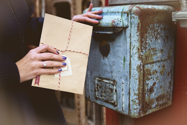 la donna getta una busta di Babbo Natale in una vecchia cassetta delle lettere d'epoca Foto Gratuite