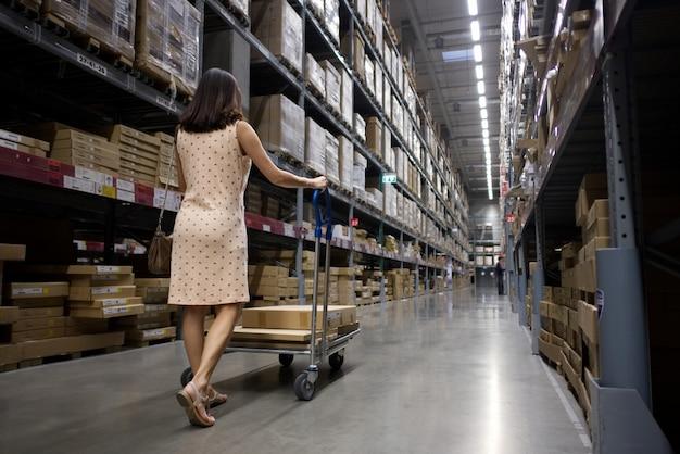La donna graziosa asiatica integrale che spinge un carrello sta cercando alcuni oggetti in magazzino Foto Premium