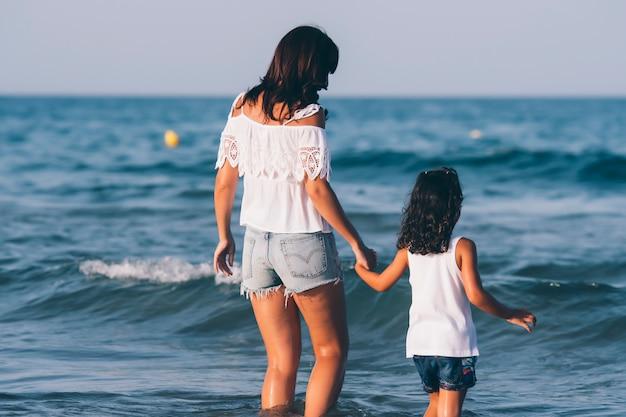 La donna graziosa con i jeans corti e sua figlia che posano sull'acqua della spiaggia Foto Premium