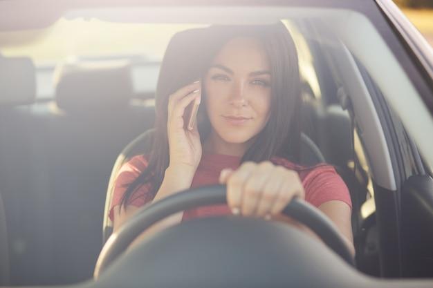 La donna guida un'auto, ha una conversazione telefonica, è piena di ingorgo, guarda attraverso la finestra Foto Gratuite