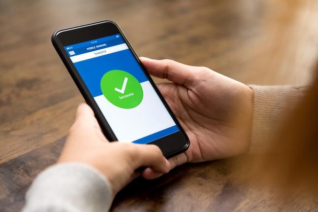 La donna ha trasferito con successo denaro online tramite l'applicazione bancaria elettronica su smartphone Foto Premium