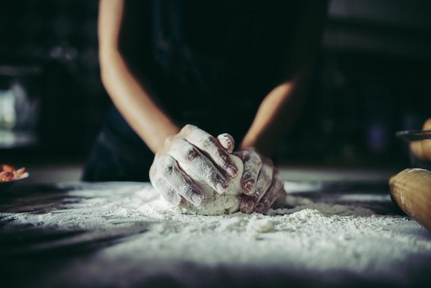 La donna impasta la pasta per fare la pizza su legno. concetto di cottura. Foto Gratuite