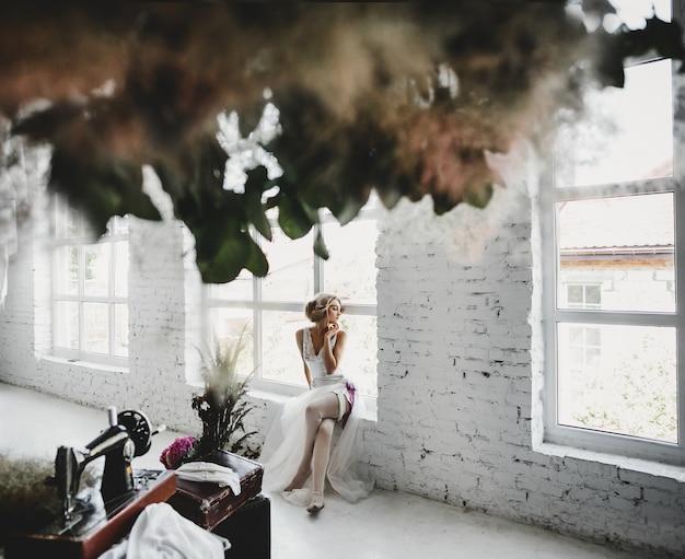 La donna in abiti bianchi si siede sul davanzale della finestra in una stanza con fiori e macchina da cucire Foto Gratuite
