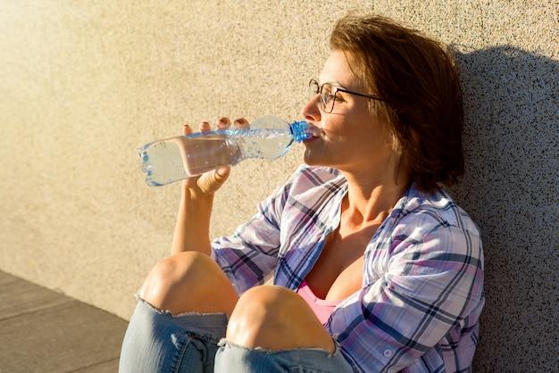 La donna in buona salute adulta beve l'acqua dalla bottiglia. Foto Premium