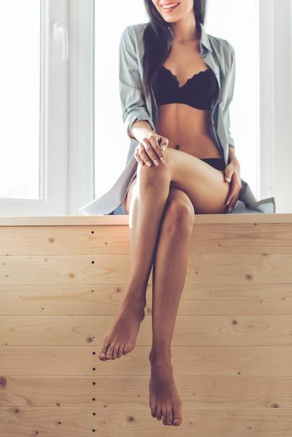 La donna in lingerie nera e camicia sbottonata sta sorridendo. Foto Premium
