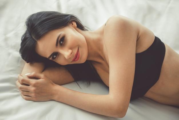 La donna in lingerie nera sta guardando sensualmente la fotocamera. Foto Premium