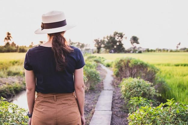 La donna in piedi sul sentiero nel campo di riso e la luce della sera Foto Premium