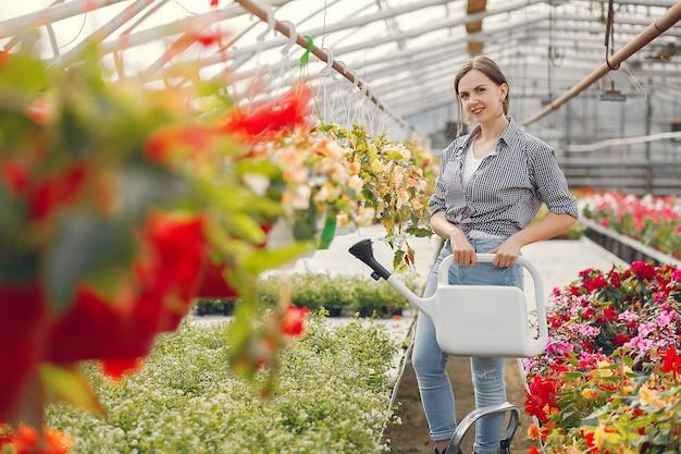 La donna in una camicia blu versa i vasi da fiori Foto Gratuite