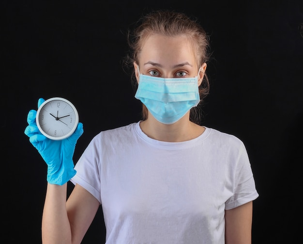 La donna in una mascherina protettiva medica, guanti tiene l'orologio bianco su una parete nera. Foto Premium