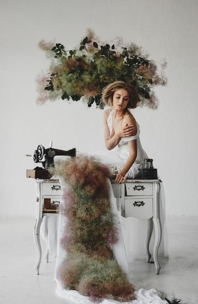 La donna in vestiti bianchi si siede in una stanza con i fiori e la macchina per cucire Foto Gratuite