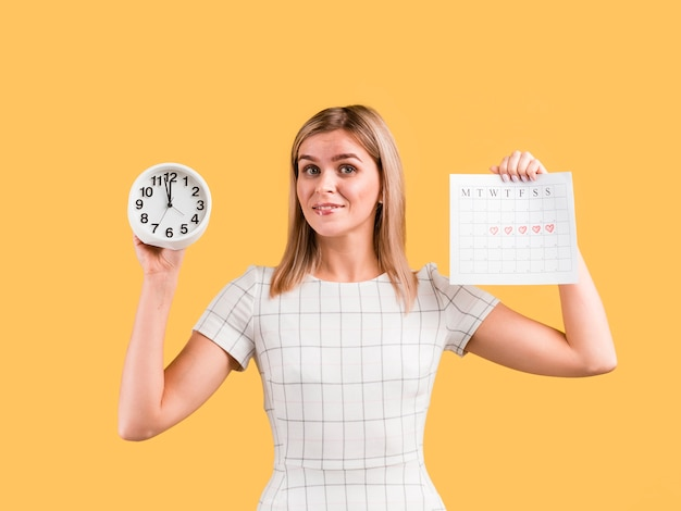 La donna in vestito bianco mostra l'orologio e il calendario Foto Gratuite