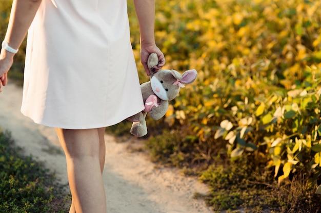 La donna incinta in vestito dentellare tiene il coniglio grigio nel suo braccio tenero Foto Gratuite