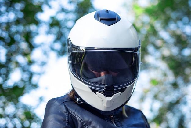 La donna indossa il casco da motociclista e allaccia la chiusura Foto Premium