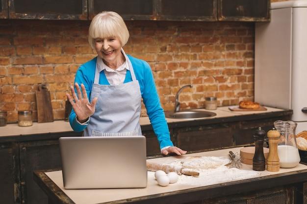 La donna invecchiata senior attraente sta cucinando sulla cucina. nonna che produce una cottura saporita. usando il laptop. Foto Premium