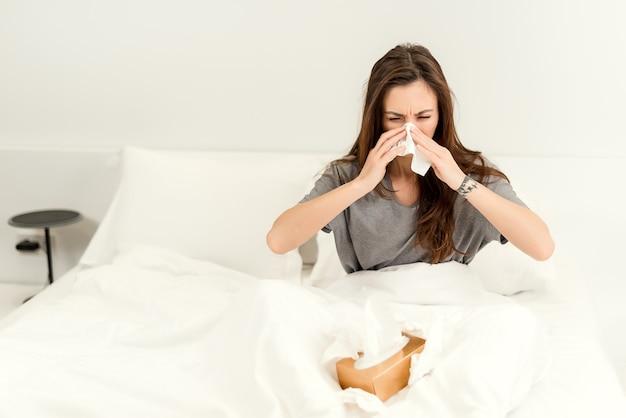 La donna malata usa i tovaglioli per pulirsi il naso e starnutire nel letto in camera da letto Foto Premium